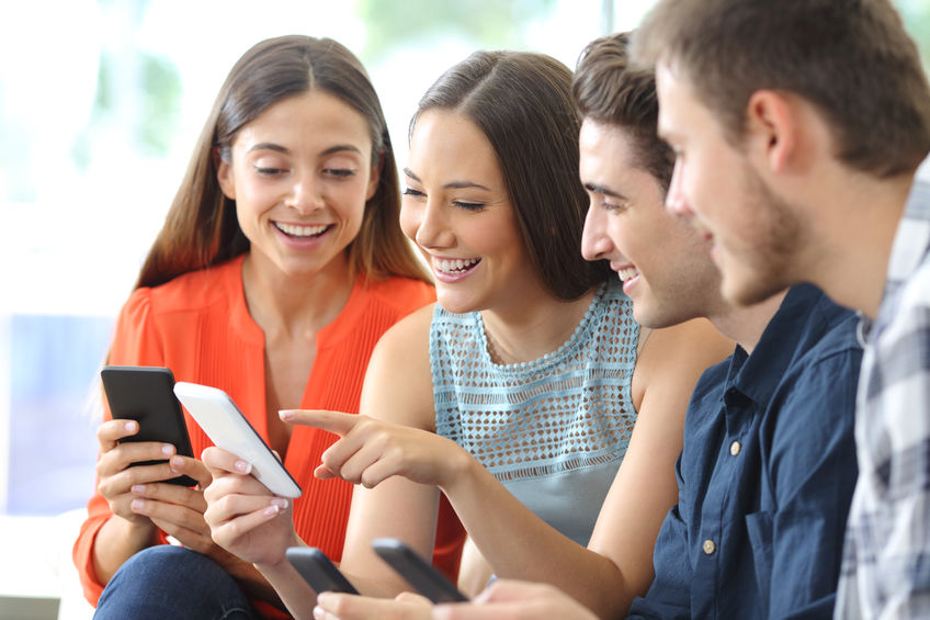 Happy group of friends checking smart phones at home